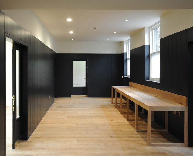 The black MDF is offset by bespoke oak furniture.