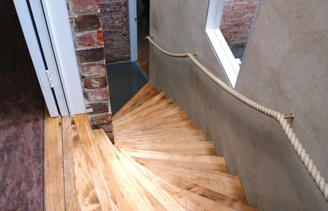 Top-lit radiating stair with treads made from reclaimed timber.