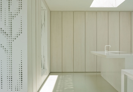 Oak panels in the kitchen contrast with the perforated metal.