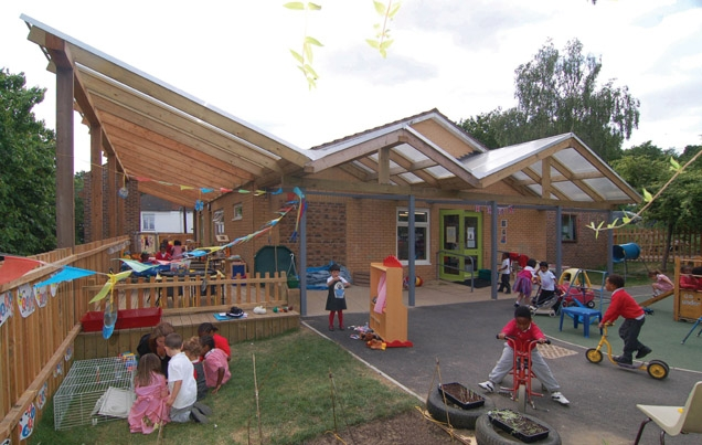 A new canopy wraps around two sides of the building, picking up on the pitched rhythm of the existing nursery.