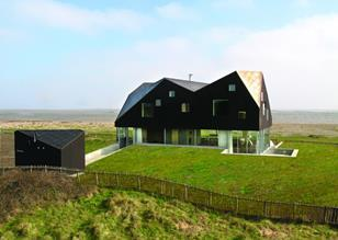 The faceted roof floats above a glazed ground floor, partially sunk into the surrounding dunes..
