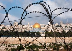 A history of division and conflict: The Old City of Jerusalem, including the Dome of the Rock, seen through coils of razor wire.