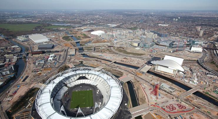The stadium sits on its own island at the southern end of the Olympic Park. The Aquatics Centre and Orbit sculpture are to its right.